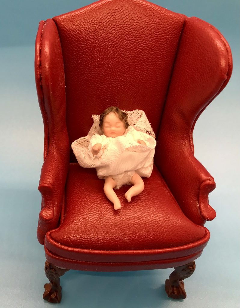 Baby in chair showing diapers