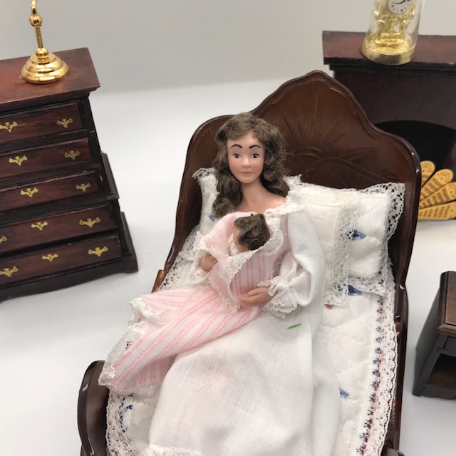 mother doll holding newborn in bed