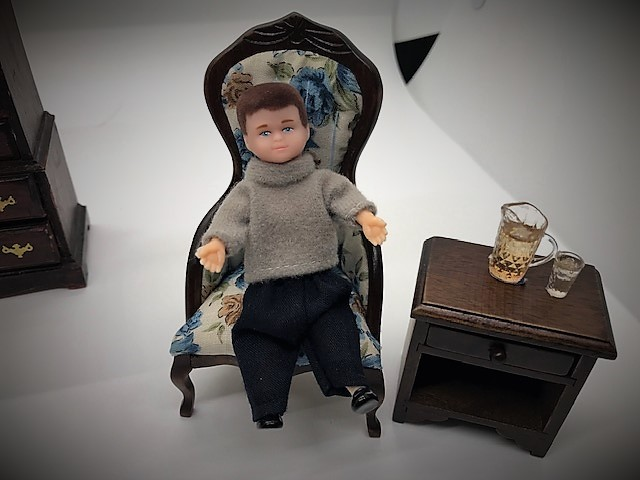 Boy doll in chair with drink